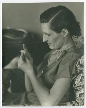 Black and white photo of a woman with her hair pulled back, sitting on a floral chair looking at her hands.
