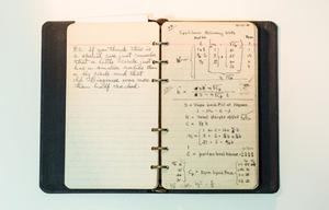 A small black notebook, open to lined pages. Handwriting is on the left page, notes on the right page.
