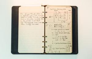 Un pequeño cuaderno negro, abierto a páginas rayadas. La escritura a mano está en la página, las notas en la página derecha.