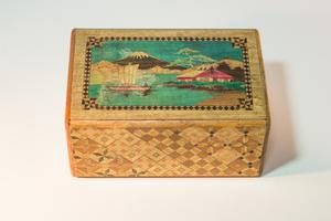 A wooden puzzle box, the top of it has an illustration of a ship on the water, a building with a red roof near it.