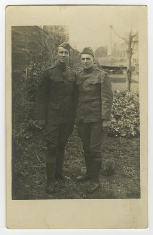 Black and white postcard with a photo of two soldiers in uniform standing side by side each other.