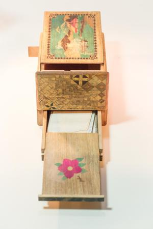 An open wooden puzzle box, the top of it has an illustration of a ship on the water, a building with a red roof near it. The part of it that's opened has a pink flower painted on it.