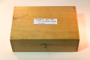 Wooden box, with a metal handle on the front of it. The top of the box has a white slip on it, with the name date and title.