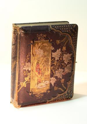 Brown worn leather book, the front of it has an intricate gold design, some of it looking like leave. There is also a bird design.