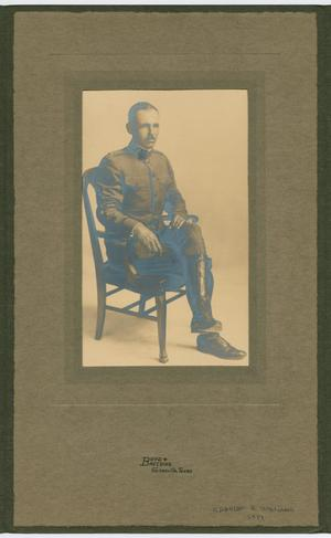 Photo of a man in uniform sitting on a chair. The photo is on a grey page.