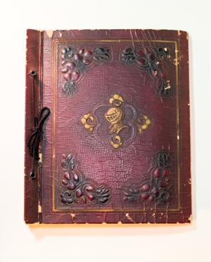 Dark red leather book, old and worn. The spines has holes looped through with string, The front cover has a black design in each corner, and a golden design in the middle in the shape of a helmet.