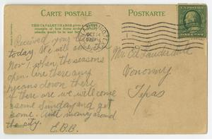 The back of a postcard, a green stamp in the top right. There is handwriting in pencil on it. The top of it has some green text.