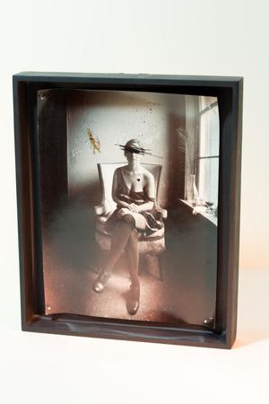 Photo in a thick black frame. The photo is of a woman with long slocks and black shoes. She is sitting on a white chair by a window. Her face is crossed out by black markings.