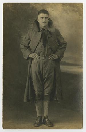 Black and white photo of a man in a soldier uniform and a coat, no hat on. He also has on black boots and his hands on his waist.