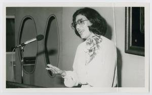 Black and white photo of a woman with glasses and a white blouse, a microphone in front of her. Her mouth is open, talking.