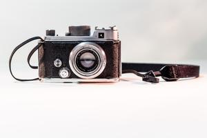 A black and silver camera, a thin small strap on the left side and a thicker strap on the right.