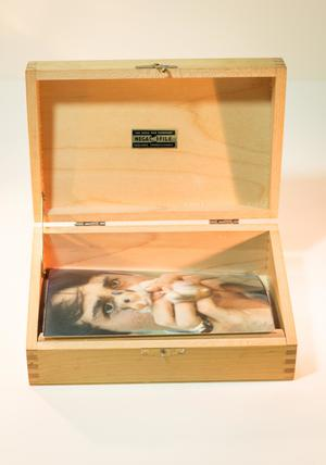 Open wooden box. The inside of the lid has a back and gold sticker. The box contains a photo of a man holding a hamster.
