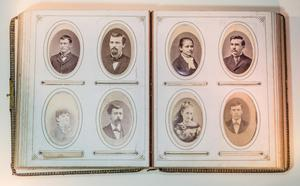 Open photo albums, showing two open page with four oval shaped photos on each page.