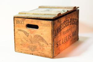A wooden box, the side of it has a hole open for a handle. The front of it has the name printed on it in black. The lid is slightly open.