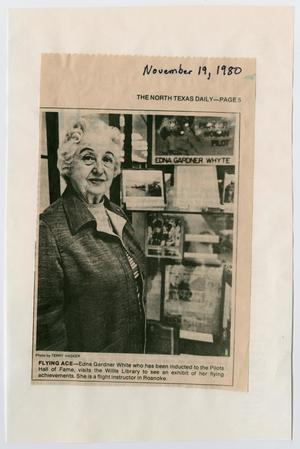 Newspaper clipping with a black and white photo of an old woman standing in front of some photographs.