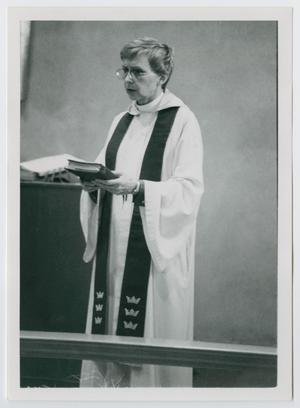Black and white photo of a women in a white robe, holding a bible in her hand.