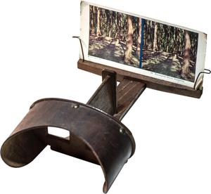 A black stereoscope viewer, a photo on display on it.