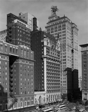 Black and white photo of a row of tall buildings, taken from above street level. Cars and busses are on the street level. The buildings are brick or stone, and all have windows covering all visible sides. The furthest and tallest building has a pegasus sign on it's top.