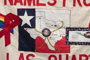Closeup of a banner, a patch in the shape of the Texas Flag is seen with the figure of Texas on it.