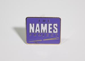 A square-shaped purple pin that says The Names Project, with a needle underneath it.