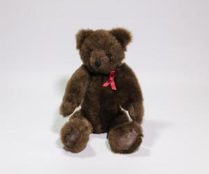 A small, brown, fuzzy bear with a red ribbon on its left side.