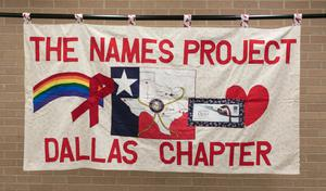 A white banner titled The Names Project at the top and Dallas Chapter at the bottom in big red letters. The middle of it is a rainbow on the side, a flag of Texas in the middle, and a red heart on the side.
