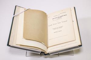 Small booklet laying on an open book. The page on the left is blank, the page on the right is a title page.