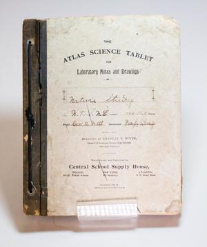 El frente de un libro, con cubierta blanca y lomo negro. El libro está muy gastado y lleva el título Libreta de ciencia atlas.