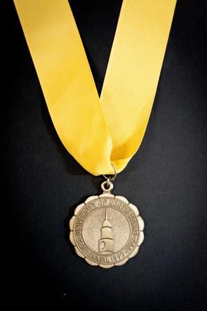 A bronze medallion with the words University of North Texas on it, as well as a drawing of a tower. It is attached to a golden yellow ribbon.