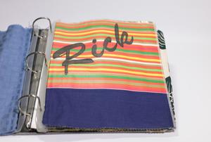 An open binder containing fabric instead of pages. The page on the right is in focus, the fabric is colorful stripes with a partiial dark blue fabric at the bottom. The word Rick is on it in black letters.