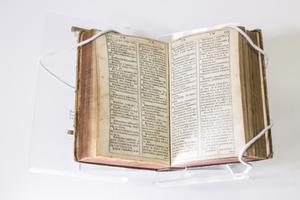 A book open, both pages filled with two columns of text on each.