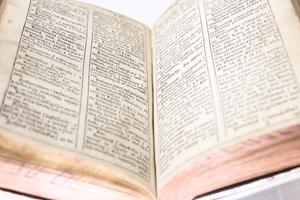Closeup of two pages of an open book, they both have two columns of text on each.