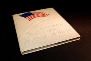 White and textured book cover. At the top is a US flag with no stars on it. Below it, slanted, are the words The Men and Women. The rest of the title is below it. This is seen from a slanted view.