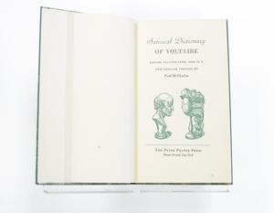 An open book, the page on the left is blank and the page on the right is a title page. the title is in green with green illustrations on it.