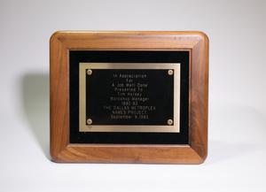 A black plaque with a wooden frame. The black part of it has the award details on it, framed by a silver line.