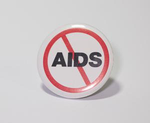 A white button, with a red circler with a slash across the middle on it. The word AIDS is on it in the middle in black letters.