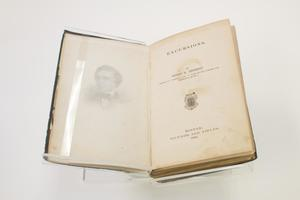 An open book, the page on the right that had the title at the top saying Excursions. The page on the left has a faded drawing of a man.