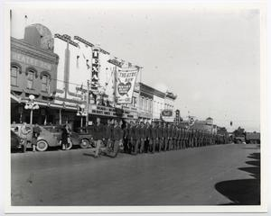 A group of men in uniform are seen marching down a street by buildings  that are side by side each other.