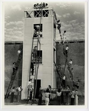 Black and white photo of several women climbing up a white tower, that is in front of a wall.