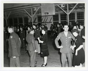 Black and white photo of men and women dispersed throughout a room. The men are wearing military uniforms. The woman are wearing black dresses.