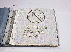 A white fabric in a binder with a cloud like patter on it. The sign for no is at the top, under it are the words Hot Glue Sequins Glass.