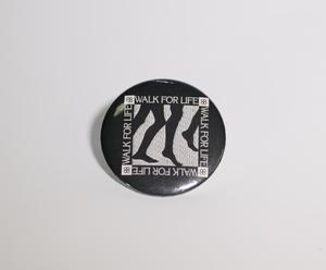 A black button, with thye Words Walk For life on it four times, in the shape of a box. In the middle is a graphic of two pairs of legs.