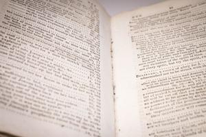 Closeup of an open book, both pages filled with typed up text.