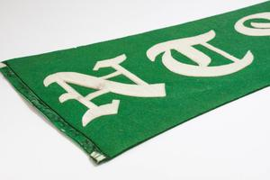 Partial view of a green triangular banner. From this view the letters N and T can be seen.