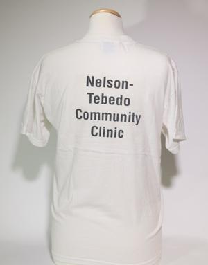 The back of a white tshirt with the words Nelson-Tebedo Community Clinic on it in black letters.