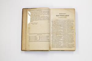 A book open to two pages. The page on the left has some text at the top. The page on the right is titled Dictionary at the top with two columns of text under it.
