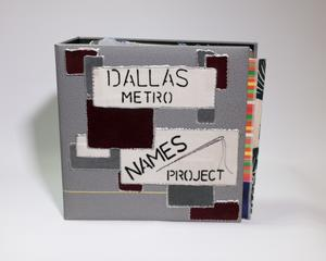 A grey binder with different patches on it. White patches contain the title. One at the top says Dallas Metro, the one on the bottom says Names Project.