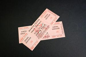 Two pink game tickets with black text and a darker pink text in the corners. One is laying across the other.