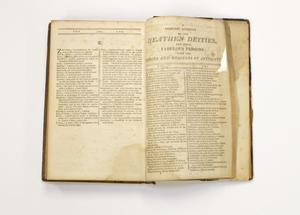 A book with old and worn pages, the page on the left containing two columns of text. The page on the right is titled Heathen Deities, with two columns of text under it.