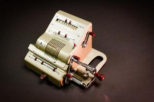 Side view of a mechanical calculator that is silver in color with red knobs.